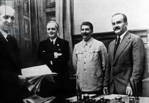 Joachim von Ribbentrop (left), German Minister for Foreign Affairs, Joseph Stalin (center), and Soviet Foreign Minister Vyacheslav Molotov (right), after the signing of the Nazi-Soviet non-aggression pact at Moscow, 23 August 1939