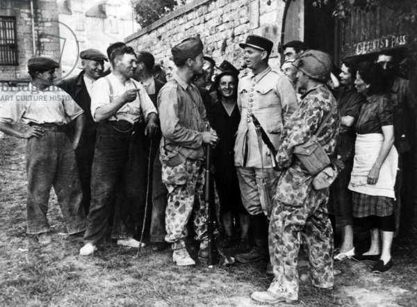 French soldiers of the 2nd armored division speaking with civilians shorthly after their landing in Normandy, august 1944