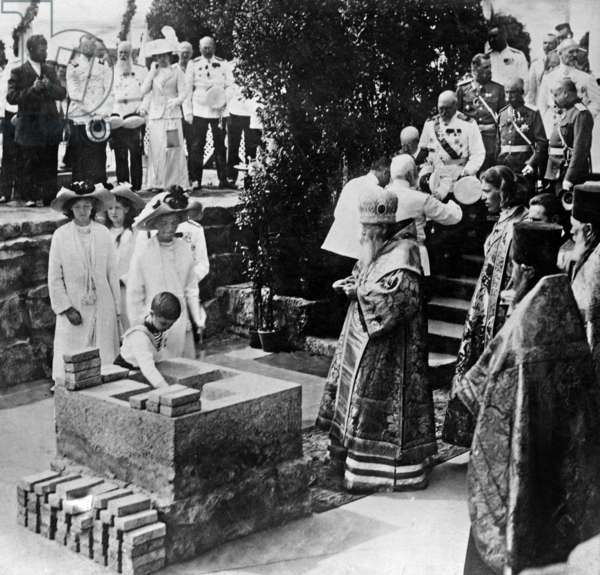 Czarevitch Alexis Nicolarevitch of Russia (1904-1918) followed by his sisters, the grand duchesses, putting the 1st stone of the alter of the cathedral in Revel (Tallinn) 1910