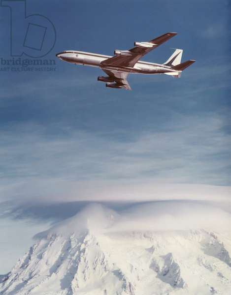 Boeing 707 flying over mountains