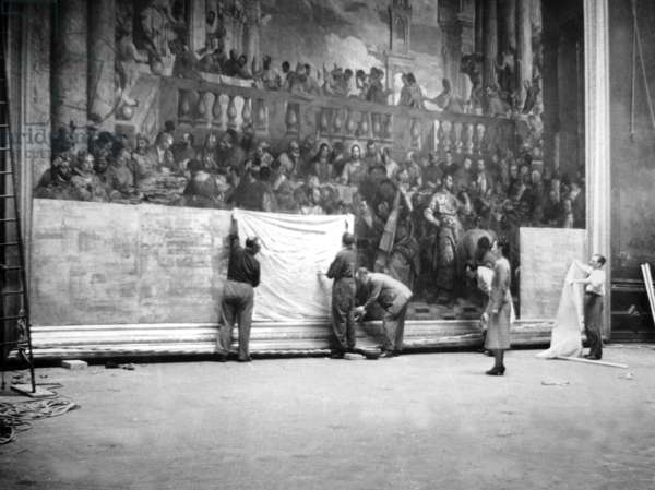 Caretakers and curators of the Louvre museum packing and wrapping the works of art (here 'The Wedding at Cana' by Veronese) before their evacuation, forecasting the possible bombings in 1939 (b/w photo)