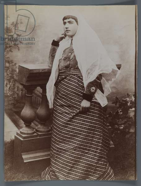 Studio shot of a woman with a white Charhad leaning against a wooden balustrade in western costume (silver albumen photo)