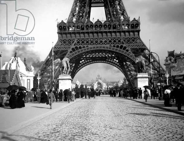 At the foot of the Eiffel Tower. Universal Exhibition of 1900, in Paris (France). On the theme of the balance sheet of a century, this exhibition, from April 15 to November 12, 1900, is designed to reflect the 20th century and pours into splendour and gigantism. Geographically, this exhibition has no centre, but the Seine acts as the main axis, and the exhibition occupies the space of the four previous exhibitions, an area of more than 112 hectares and covers a whole area of the capital, the Gros Caillou (i.e., the Champs Elysees, the Esplanade des Invalides, the quays, the Trocadero and the Mars fields). More than 36 entrance gates, the most important Porte Monumentale, south west of Place de la Concorde. The number of visitors will reach a record 50 million, with more than 83,000 exhibitors, 46% of whom are French.
