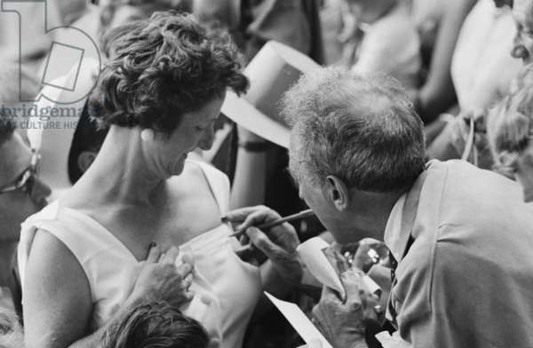 Jean Cocteau signing an autograph at a bullfight, Vallauris, France, 1955 (b/w photo)