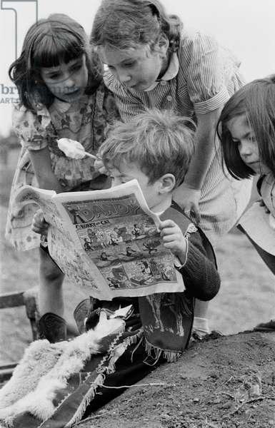Children reading a comic book at Lollard Adventure Playground, Lambeth, South London, UK, 1955 (b/w photo)