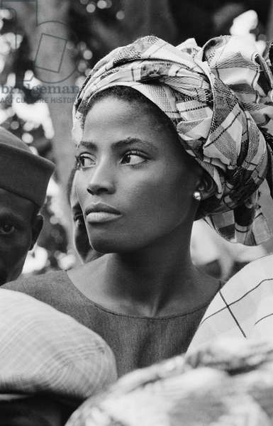 Spectator waiting for Queen Elizabeth II at a Myohauang Day service in Lagos Cathedral, Nigeria, 1956 (b/w photo)