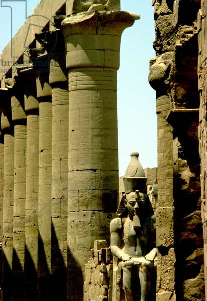 Luxor, Thebes: Temple of Luxor. Colossal statue of RAMSES II (20th Dynasty) and large colonnade of ALL-ANKH-AMON (18th Dynasty).