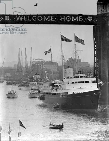 Under the Welcome Home sign on the Tower Bridge slowly moves the Royal Yacht