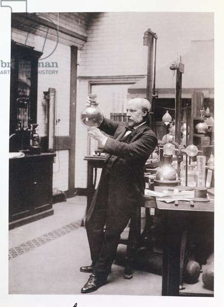 Portrait of Sir James Dewar (1842-1923) holding a flask in his private basement laboratories of the Royal Institution, 1902 (photogravure)