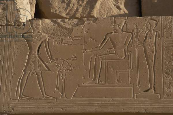 Ramesseum. Relief depicting the pharaoh making an offering to the gods Amon, seated, and Ptah. Medinet Habu. Egypt.