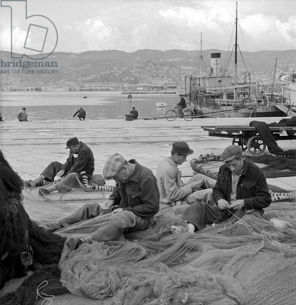 Fishermen getting their nets ready to go fishing, Trieste, Italy, 1948-49 (b/w photo)
