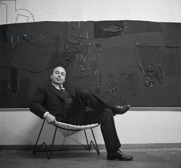 Toti Scialoja sitting in front of one of his paintings, Burri Studio at Via Margutta, Rome, 1950s (b/w photo)