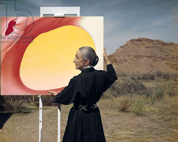 Georgia O'Keeffe holding her painting, Taos Pueblo, New Mexico, 1960 (photo)