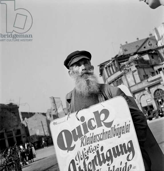 Man holding an advertising sign in Frankfurt, 1948-49 (b/w photo)