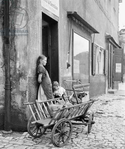 Two children wait outside a grocery store with the family shopping cart, Hoescht, Germany, 1946 (b/w photo)