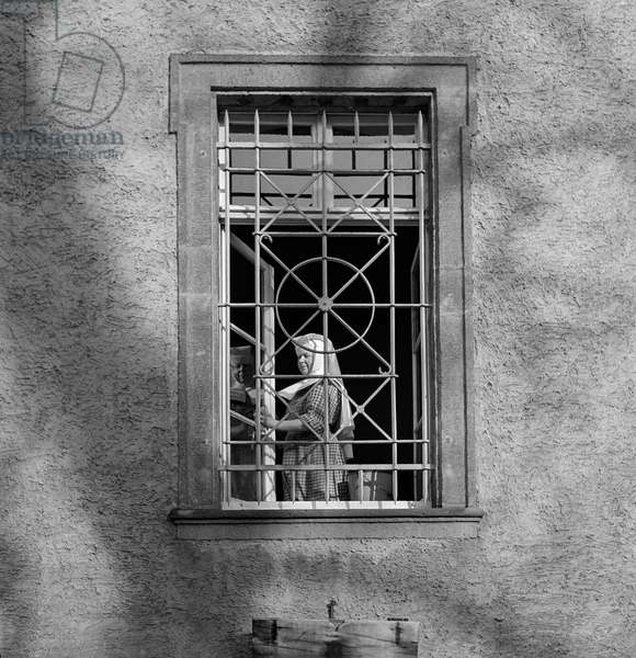 A nun standing in the frame of a window at the Maria Laach abbey, Germany, 1947-49 (b/w photo)