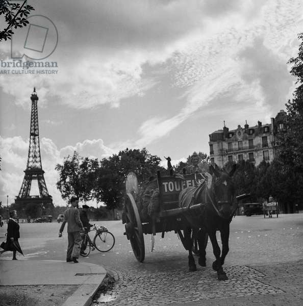 A horse carriage passing by with the Eiffel Tower in the background, Place de l'Alma, 1945 (b/w photo)