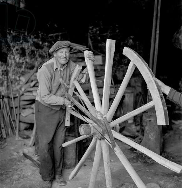 Maestro Michele working on the wooden wheel of a horse carriage, 1947 (b/w photo)