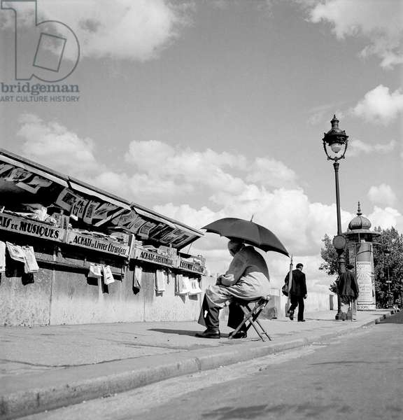 Magazine stand along the Seine river in Paris (b/w photo)