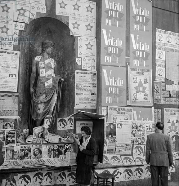 Poster for the PRI all over an old Roman statue, Rome, 1948 (b/w photo)