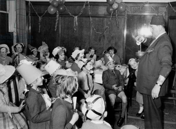 Conjurer entertaining children, UK, 1958 (b/w photo)