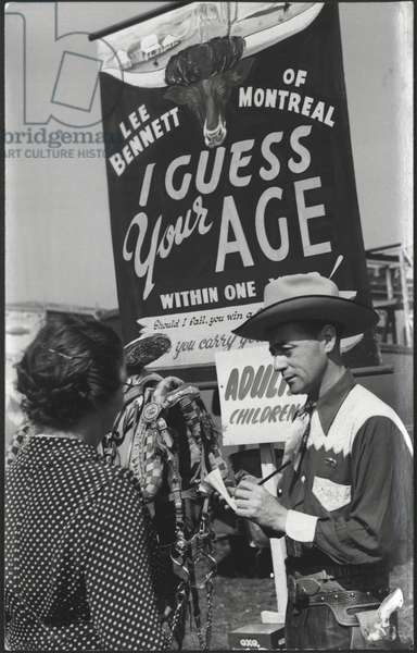 Lee Bennett guessing a woman's age at his 'I Guess Your Age' attraction at the Hoppings Fair, UK, c.1940s (b/w photo)