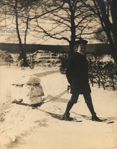 A young boy with a Sled in the Snow (b/w photo)