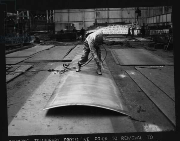 Workers spraying temporary protective prior to removal to a building berth, Hawthorn Leslie Yard, Hebburn, UK, July 1962