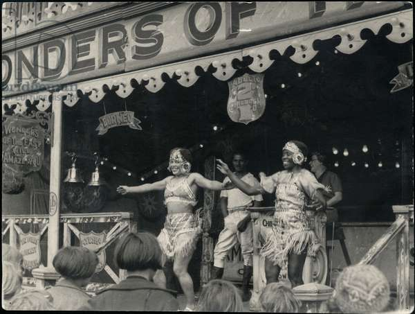 'Wonders of the East' performers entertain the public at the Hoppings Fair, UK, c.1940s (b/w photo)