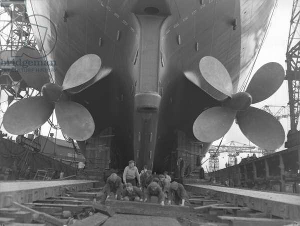 Preparing the slipway for a launch, Newcastle, UK, 1961 (b/w photo)