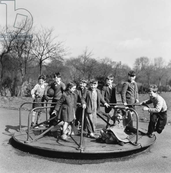 Children on roundabout, Leazes Park, Newcastle, 1956 (b/w photo)