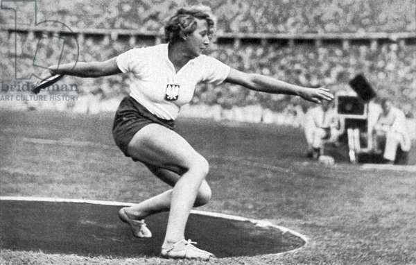 Berlin, Germany: 1936 Polish and Jewish athlete Hedwiga Wajsowna throwing the discus at the 1936 Olympics. She won the silver medal in the event.  (b/w photo)