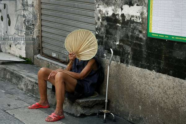 An elderly woman hiding her face in Guangzhou, China. October 17, 2009.  (photo)