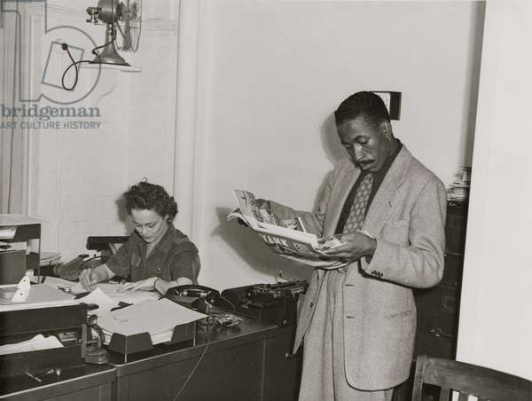 Gordon Parks, Farm Security Administration/Office of War Information photographer, standing in office with Helen Wool seated at desk, 1943 (b/w photo)