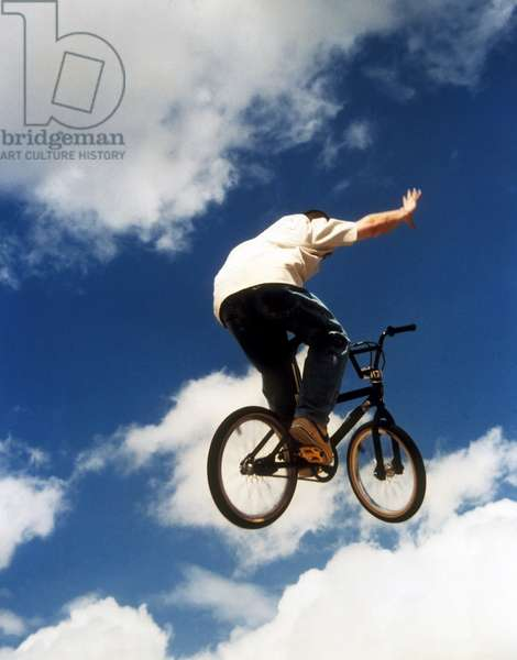 BMX rider releasin his hand from the handle bars while in mid air, UK 2000's.