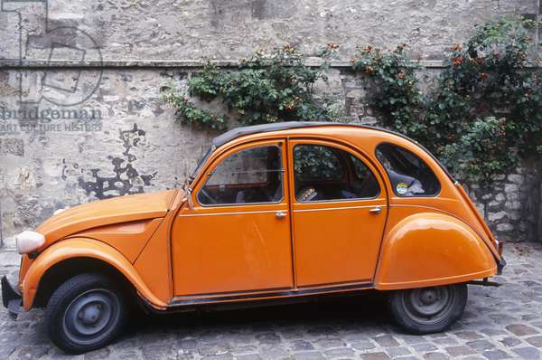 France, an orange Citroen 2CV parked in a cobbled street