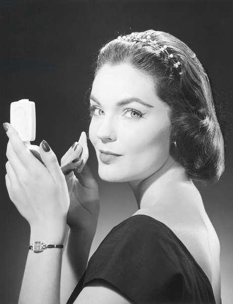 Woman applying make-up (b/w photo)