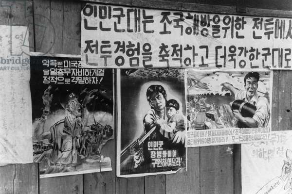 Anti-American propaganda posters on a wall in a town in the Korean People's Democratic Republic urging people to protect children from American atrocities and to intensify the production of ammunition. Korean War, January 1951.