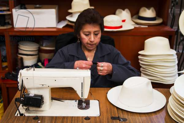Woman sewing the black brim on to a panama hat (photo)