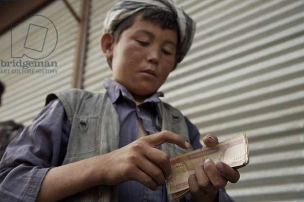 A young boy counts his earnings as porter, at the main market of Mazar-e-Sharif, in the northern province of Balkh. An estimated 60,000 children have fled broken families, poverty and conflict, and now live or work in the streets of major cities. Afghanistan. June 26, 2007.  (photo)