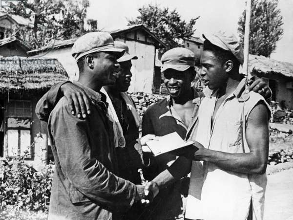 Korean War. African American prisoners in a North Korean POW camp exchanging addresses after the news of the signing of the armistice. August 1953.