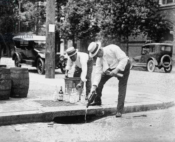 Agents Pouring liquor down a sewer on the Street 1921 (photo)