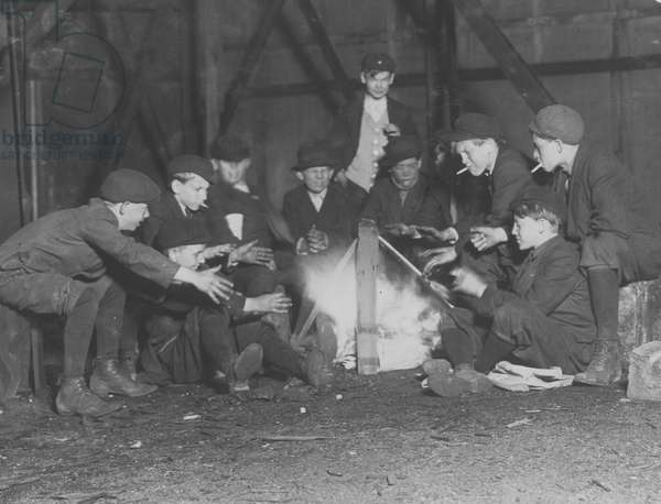 Jefferson St. Gang of newsboys at 10:00 P.M. over campfire in corner lot behind bill-board. 1910 (photo)
