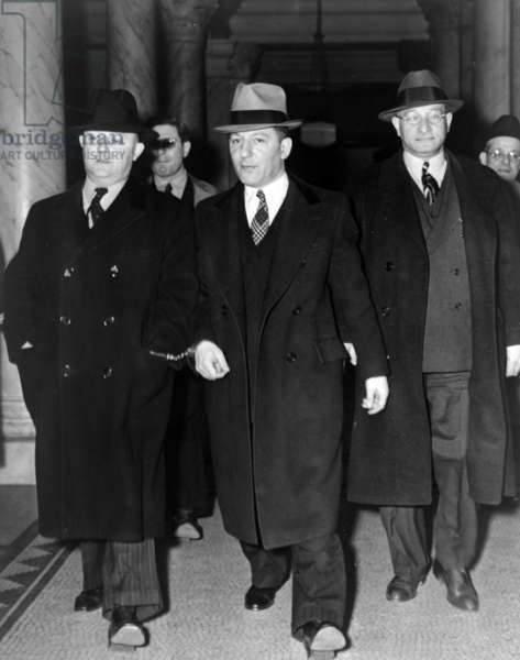 """19400101 Louis """"Lepke"""" Buchalter, centre, handcuffed to J. Edgar Hoover, on the left, with another man on the right, at entrance to courthouse."""