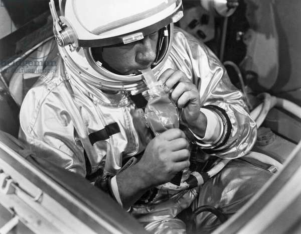 A NASA test subject consumes a meal of pot roast and gravy through a feeding tube pack aboard a Gemini spacecraft mockup (b/w photo)