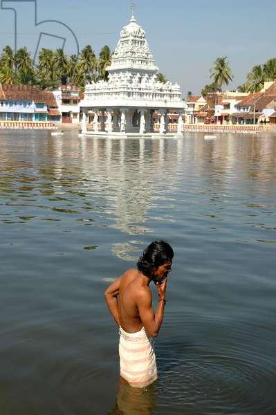 Man bathing at Hindu temple tank near Kanyakumari. India. January 14, 2005.  (photo)