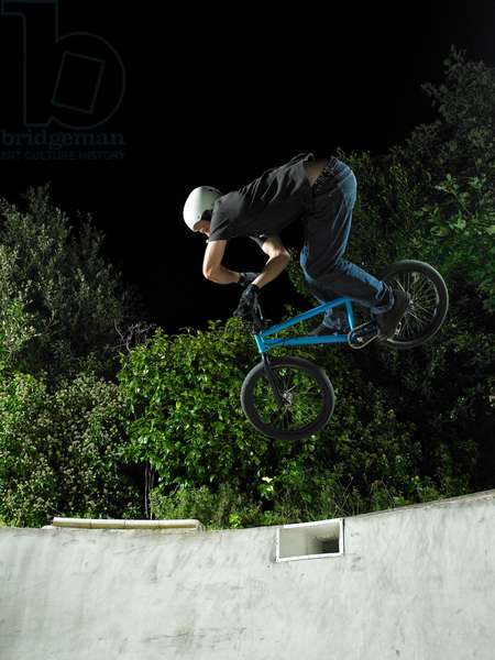 Man on blue bmx doing an x-up air in a backyard pool at night, UK