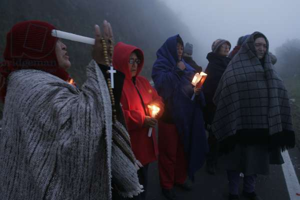 A group of women offering prayer for the victims of a devastating volcanic eruption. The Tungurahua, an active volcano, in the Cordillera Central (a chain of mountains, in the Andes) of Ecuador, erupted on July 14th and August 16th of 2006, devastating life in the small towns on its slope and surroundings. A river of fire was formed by over 10 million cubic meters of ash, gravel and incandescent material. More than 3000 people were evacuated from the area with six casualties and around 60 missing. With the alarm of another eruption ahead, the residents enter the emergency zone to work and take care of their homes. By nightfall they return to rest at the volcano's feet. Tungarahua Province, Ecuador. August 17, 2006.  (photo)