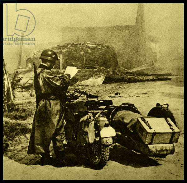 German solider stands next to a motorbike, outside a devastated town in France. Taken during the invasion of France 1940.