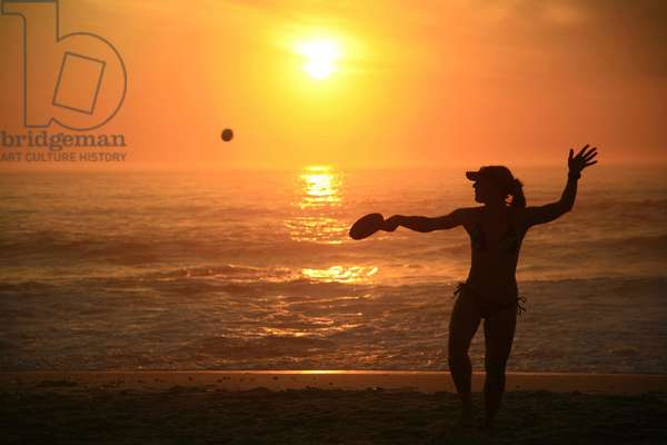 A woman playing beach bats on Clifton Beach, in Cape Town, South Africa. September 4, 2006.  (photo)